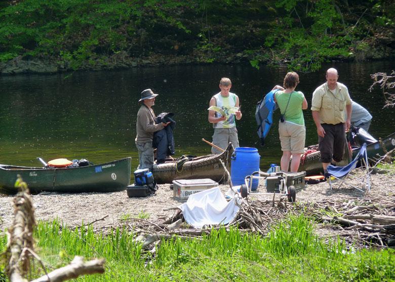 kano's en kajaks worden over de dam gedragen
