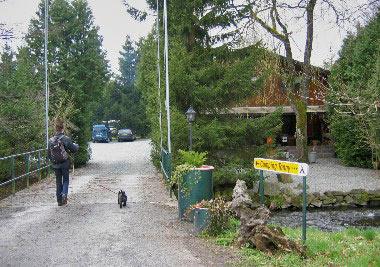 Ingang van de camping, een brug over de beek met rechts het hoofdgebouw