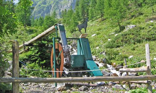 naast het waterrad een generator waarmee stroom wordt opgewekt